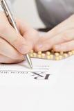 Medical doctor filling out drug prescription - studio shot Royalty Free Stock Images