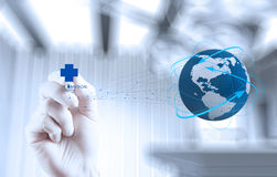 Medical Doctor hand drawing the world globe. In his hands as medical network concept stock photos