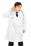 Medical doctor holding hand at ear and listening Stock Images