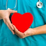 Medical doctor holding a heart symbol. On white background Stock Photo