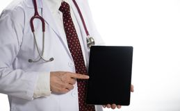 Medical doctor holding tablet facing the front on white background royalty free stock photos