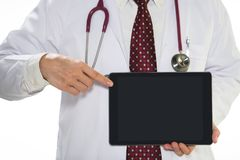 Medical doctor holding tablet facing the front on white background royalty free stock photography