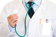 Medical doctor holding up stethoscope. Close-up. Royalty Free Stock Photos