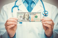 Medical doctor holding USA dollars in his hands. Medical doctor with a stethoscope holding USA dollars in hands Stock Photo