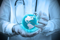 Medical Doctor holding a world gobe in her hands Stock Image