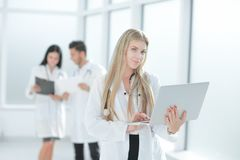 Medical doctor with laptop standing in the hallway of the clinic. Photo with copy space royalty free stock images