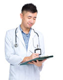 Medical doctor looking at clipboard Stock Photos