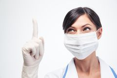 Medical doctor in mask pointing finger up Stock Image