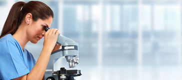 Medical doctor with microscope. Scientific doctor woman with microscope in medical laboratory Stock Image