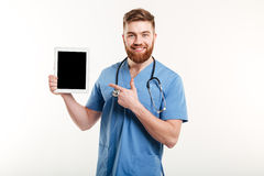Medical doctor or nurse pointing finger at blank screen tablet Stock Photos