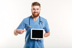Medical doctor or nurse pointing finger at blank screen tablet Royalty Free Stock Images
