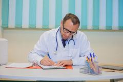 Medical doctor pharmacist writing prescription in his office. Stock Photography