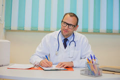 Medical doctor pharmacist writing prescription in his office. Royalty Free Stock Images