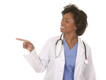 Medical doctor pointing. Black doctor wearing scrubs and lab coat on white isolated background Stock Image