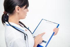 Medical doctor reading notes on clipboard Royalty Free Stock Photos