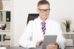 Medical Doctor Reading Reports Using Tablet. Medical Doctor Reading Client Progress Reports Using Tablet Stock Photos