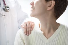 Medical doctor reassuring senior patient and putting a hand on patient's shoulder stock photography