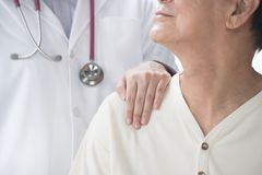 Medical doctor reassuring senior patient and putting a hand on patient's shoulder royalty free stock photography