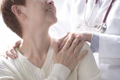 Medical doctor reassuring senior patient and putting a hand on patient's shoulder stock photo