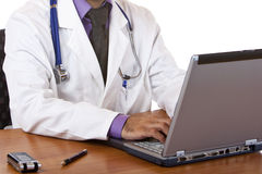 Medical doctor reviewing his notes on laptop Royalty Free Stock Images
