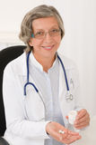 Medical doctor senior female hold pills smiling Royalty Free Stock Image