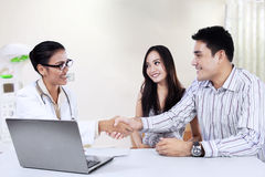 Medical doctor shaking hands with a couple Royalty Free Stock Photos
