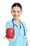 Medical doctor showing apple. Doctor - nurse woman giving / showing apple. Young female medical professional isolated on white background Royalty Free Stock Photo