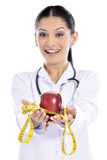 Medical doctor showing apple. Doctor - nurse woman giving / showing apple. Young female medical professional isolated on white background Stock Photos