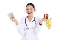 Medical doctor showing apple and pils Royalty Free Stock Photos