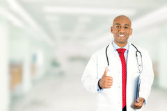 Medical doctor showing thumbs up standing in hospital hallway Royalty Free Stock Photography