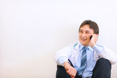 Medical doctor sitting on floor and talking mobile Stock Images