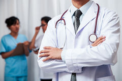 Medical doctor stand folding his arms Stock Photo