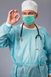 Medical doctor with stethoscope and face mask holding a pill. Gr Royalty Free Stock Images