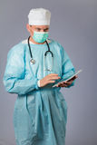 Medical doctor with stethoscope and face mask holding a tablet. Stock Photography