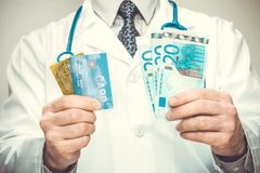 Medical doctor holding EURO in his hands - close up studio shot. Medical doctor with a stethoscope holding EURO in hands - close up studio shot Stock Photo