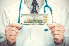 Medical doctor holding USA dollars with two hands - close up studio shot. Medical doctor with a stethoscope holding USA dollars with two hands - close up studio Stock Photo