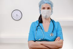 Medical doctor with stethoscope on white background. Female nurse wearing surgical mask and hat. Caucasian Woman Portrait royalty free stock photos