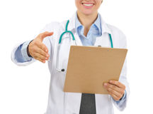 Medical doctor streching hand for handshake. Closeup on medical doctor with clipboard streching hand for handshake Royalty Free Stock Photo