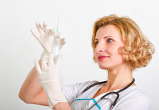 Medical doctor with syringe. Beautiful young medical doctor with syringe Stock Photography