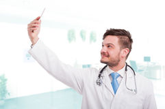 Medical doctor taking a selfie with front camera Royalty Free Stock Photos