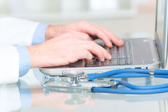 Medical doctor typing on laptop royalty free stock photography
