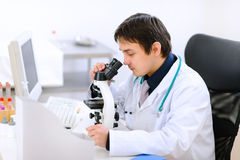 Medical doctor using microscope Royalty Free Stock Photos
