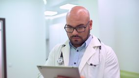 Medical doctor using tablet. Slow-motion. Male health professional using tablet in medical office stock video footage