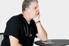 Medical Doctor wearing scrubs bored writing script. Medical Doctor wearing scrubs bored writing prescriptions Stock Images