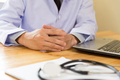 Medical doctor in white coat is holding hands together in his of. Medical doctor in white coat is holding hands together, with computer laptop in his office stock image