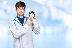 Medical doctor in white coat. With stethoscope holding out an alarm clock royalty free stock image