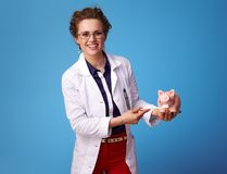 Medical doctor woman cleaning piggy banks teeth on blue Royalty Free Stock Images