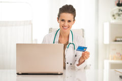 Medical doctor woman with credit card and laptop Stock Photo