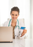 Medical doctor woman with credit card and laptop Stock Images