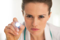 Medical doctor woman examining using flashlight Stock Photo